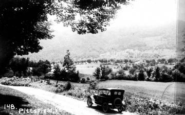 A car beside valley fields