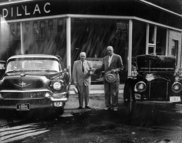 Two men in front of a Cadillac Dealer