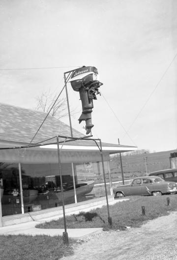 Boat Motor hanging outside of shop