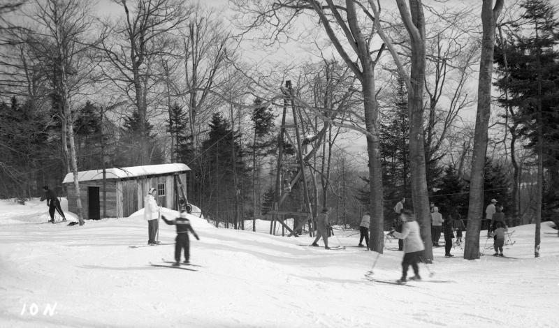 People on skies at Hogback, circa 1953. I read stories about how wooden shacks were built around the property and used as warming huts, with pot belly stoves inside burning wood continuously. There were signs nearby warning skiers not to get too close. Several learned the hard way when the back of their nylon packs had melted off. | Photo: UVM Landscape Change Program