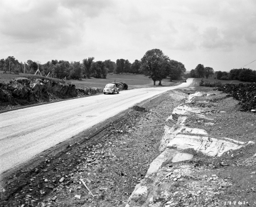 Automobile and Tractor at Road with Outcrop