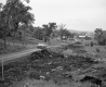 Automobiles on Dirt Road Next to Area of Loose Soil