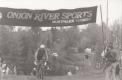 A bike racer rides under a banner