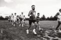 A group of fifteen runners run across a field
