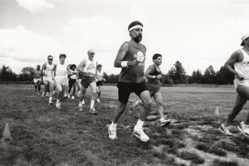 A group of fifteen runners run across a field