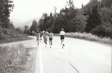 A group of runners on a paved road
