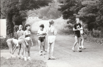 A group of eight runners stand in a dirt road